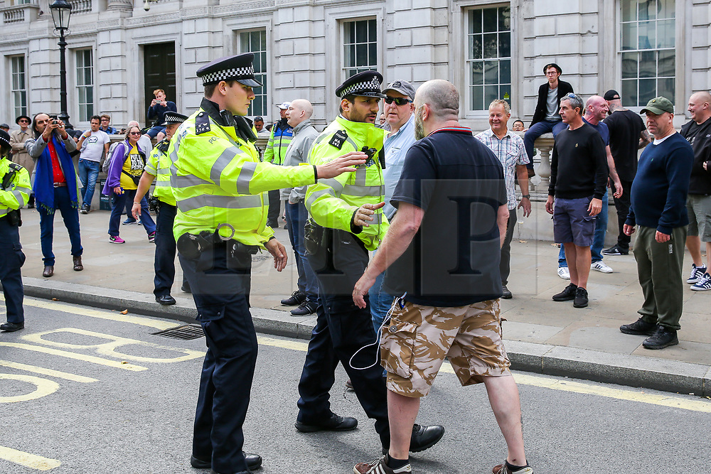 """© Licensed to London News Pictures. 07/09/2019. London, UK. A police officers confront a Pro Brexit protester in Whitehall as anti-Brexit protesters take part in """"Defend our Democracy and Stop Brexit"""" demonstration in Whitehall, Westminster. The protesters are demonstrating against the British Prime Minister Boris Johnson's intention to prorogue Parliament until 14 October. Photo credit: Dinendra Haria/LNP"""