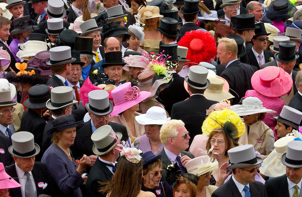 Crowd of racegoers in traditional top hats, tails and dramatic fashions at Royal Ascot Races