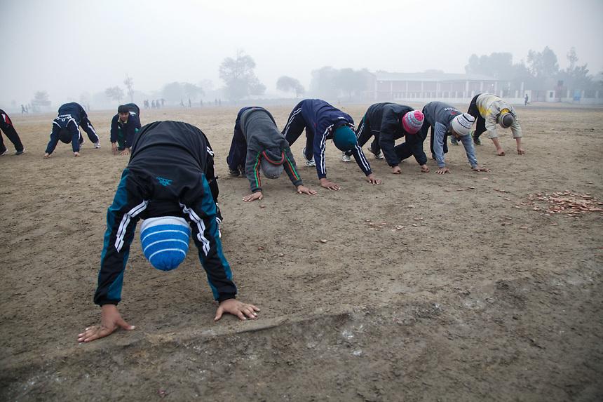Le group des petits élèves de Bhiwani Boxing Club pendant des exercices de flexion, au stade de Bhiwani