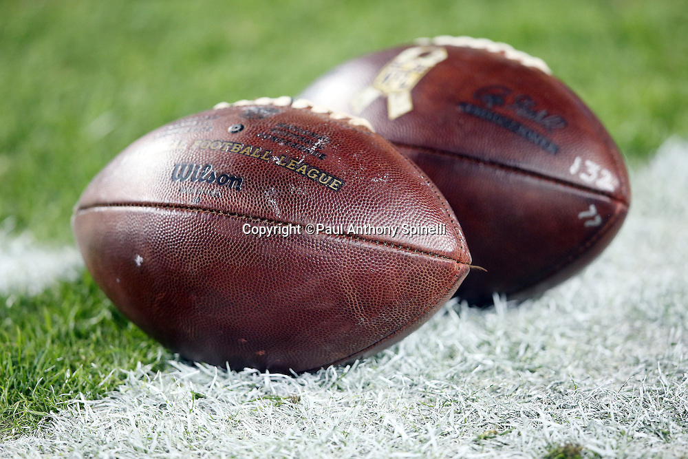 A pair of footballs lie on the sideline grass before the Washington Redskins 2015 week 13 regular season NFL football game against the Dallas Cowboys on Monday, Dec. 7, 2015 in Landover, Md. The Cowboys won the game 19-16. (©Paul Anthony Spinelli)