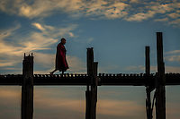 MANDALAY, MYANMAR - CIRCA DECEMBER 2013: Buddhist monk crossing the U Bein Bridge in Amarpura