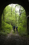 parent with child at the end of an old railroad tunnel