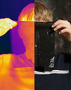A boy holding up a sheet of black plastic. This image has a corresponding visible light image.  This plastic is opaque to visible light, but is transparent to far-infrared light.  This image was taken inthe far-infrared.  The different colors represent different temperatures on the object. The lightest colors are the hottest temperatures, while the darker colors represent a cooler temperature.  Thermography uses special cameras that can detect light in the far-infrared range of the electromagnetic spectrum (900?14,000 nanometers or 0.9?14 µm) and creates an  image of the objects temperature..