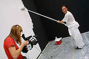 VENICE, ITALY..49th Biennale of Venice.Italian Pavillion..Nedka Solakov (here being interviewed) and an assistant paint the same room black and white circularly, over and over again, during the 5 months of the Biennale..(Photo by Heimo Aga)