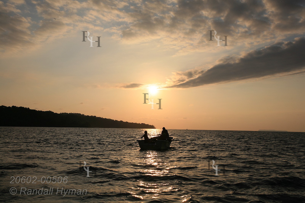 Sun sets over fishermen in boat in Drake Bay off Osa Peninsula coast in Pacific Ocean at Corcovado National Park; Costa Rica.