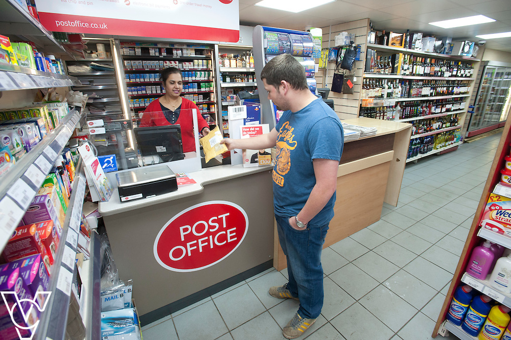 Pictured postmaster Kanchan Lakhman serving customer Martin Carter<br /> <br /> Thringstone Post Office, 19-23 Loughborough Road, Thringstone, Leicestershire.<br /> Date: January 23, 2015