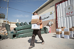 Licensed to London News Pictures. 20/10/2016. An aid worker carries food and basic hygiene kits for Iraqi refugees that have recently arrived from areas liberated from the Islamic State in Iraq during the ongoing Mosul Offensive.<br /> <br /> The crowded Dibaga camp, housing around 28,000 Sunni Arab refugees, is the main gathering point for new IDPs now fleeing areas where ISIS have been pushed out or are in conflict with the Iraqi Army. Photo credit: Matt Cetti-Roberts/LNP