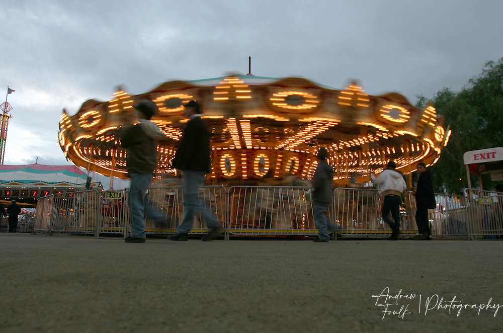 /Andrew Foulk/For The Californian/.Southern California Fair goers walk past the Mary-go-round at the fairgrounds  in Perris.