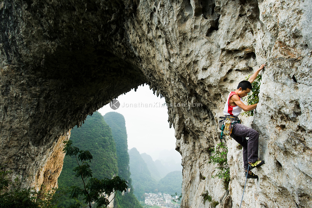 A man rock climbs on Moon Hill near Yangshuo, China (Model Released, Li Shengiang).