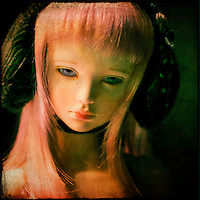 A dolls face with pink hair