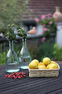 white painted basked filled with lemons, next to it a handful of red chili peppers, behind 2 old glass bottles with nature flowers. Placed on wooden outdoor table.