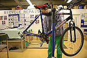 A prisoner learns how to repair bicycles in the prison workshop. HMP Wandsworth, London, United Kingdom