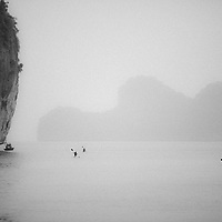 "Kayakers paddle alongside climbers ""Deep Water Soloing"" or climbing without ropes above deep water near Catba Island, Halong Bay, Vietnam"
