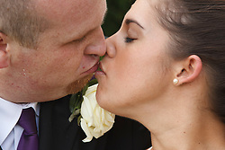 Bride who has cerebral palsy, with groom kissing at wedding ceremony.