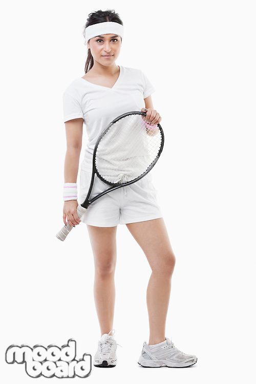 Portrait of a confident young female tennis player standing over white background