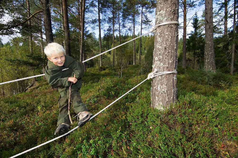 Boy in a Norwegian naturbarnehage (nature nursery) rope walking