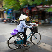Woman riding bicycle through the streets of Hanoi's Old Quarter