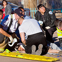 020113       Cable Hoover<br /> <br /> Gallup police and emergency personnel tend to a pedestrian that was run over by a truck at the intersection of Historic Highway 66 and Second Street in downtown Gallup Friday.