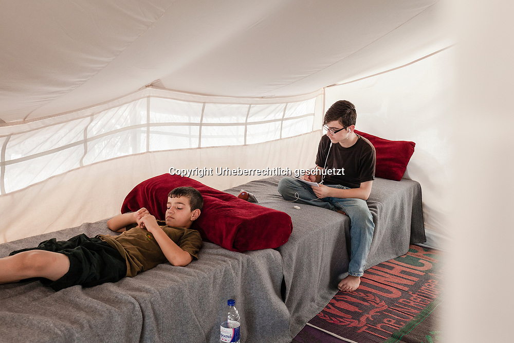 Greece, Lagkadikia, Refugee Camp, Judi, teaching himself german language via Youtube Channel. From Arabic to German inside the tent. His brother is playing on an old smartphone. His brother Mohamad, age 12, is bored from the daily routine in the camp. There is nothing to do most of the time. Hayfa Sadiq, age 34, is staying in this camp since end of April, 2016 with her five boys age between 1,5 and 15. Judi, age 15, Mohamad, age 12, Shahin, age 9, Abdul Rahman, age 6, Abdulla, age 1,5. Her husband, Mazkin, age 42, and father of the kids, is living in Berlin, Germany. He is accepted as refugee seeking asylum. They family is form Haseki, North Syria.