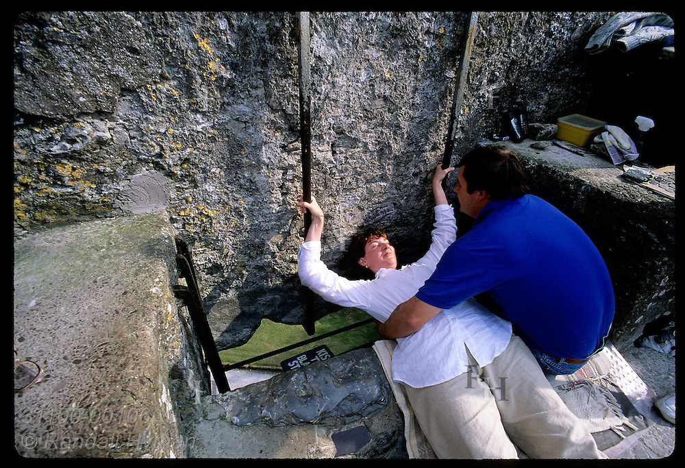 'Holder' Nigel Barrows helps woman lean back to kiss Blarney Stone atop 130' Blarney Castle. Ireland