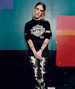 Young male punk rocker standing against wall and posing with ankles crossed.