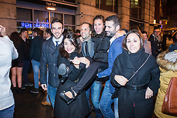 © Licensed to London News Pictures . 01/01/2015 . Manchester , UK . A woman is carried by three others along Withy Grove . Revellers usher in the New Year on a night out in Manchester City Centre .  Photo credit : Joel Goodman/LNP