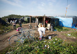 "© Licensed to London News Pictures. 30/08/2015. Calais, France. A bike is parked outside one of the shops at the camp, also known as the Jungle, at Calais. Today around a hundred British cyclists from ""Bikes Beyond Borders"" arrived at the refugee camp in a two-day ride from London to donate bicycles and supplies to support the life at the site. Photo credit : Isabel Infantes/LNP"