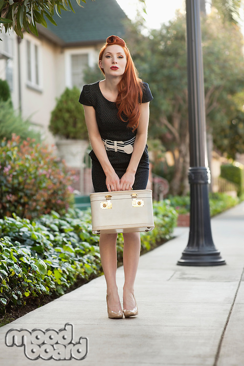 Full length of a stylish woman holding a vanity case
