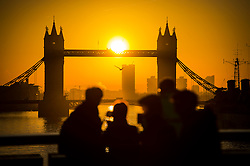 © Licensed to London News Pictures. 16/02/2016. London, UK. People gather to watch the sun rise behind Tower Bridge in central London on a cold winter morning. Temperatures in the capital dropped below zero last night. Photo credit: Ben Cawthra/LNP