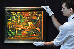 "© Licensed to London News Pictures. 17/11/2017. London, UK.  London, UK.  17 November 2017. A technician hangs ""The Goldfish Pool at Chartwell"", circa 1962, by Sir Winston Churchill (Est. GBP 50-80k), the final work Churchill ever painted.  Preview upcoming auctions of Modern & Post War British Art and Scottish Art taking place at Sotheby's, New Bond Street, on 21 and 22 November. Photo credit: Stephen Chung/LNP"