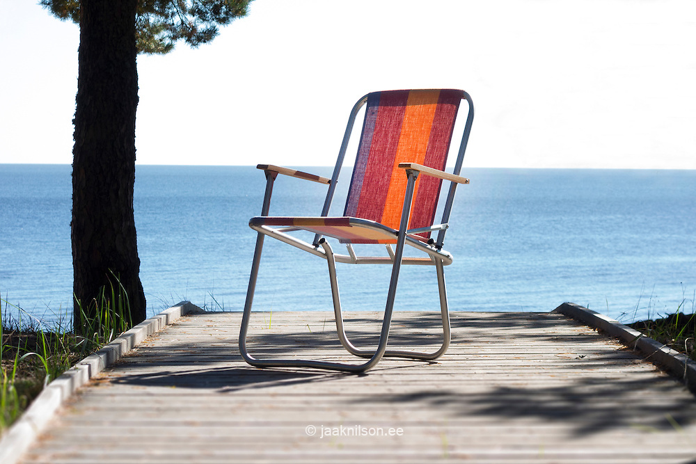 Folding beach chair on wooden boardwalk at lake Peipsi in Kauksi. Ida-Viru county, Estonia