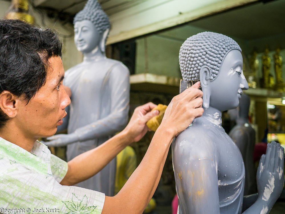 "12 NOVEMBER 2012 - BANGKOK, THAILAND:   Workers finish a statue of the Buddha at a shop on Bamrung Muang Street in Bangkok. Thanon Bamrung Muang (Thanon is Thai for Road or Street) is Bangkok's ""Street of Many Buddhas."" Like many ancient cities, Bangkok was once a city of artisan's neighborhoods and Bamrung Muang Road, near Bangkok's present day city hall, was once the street where all the country's Buddha statues were made. Now they made in factories on the edge of Bangkok, but Bamrung Muang Road is still where the statues are sold. Once an elephant trail, it was one of the first streets paved in Bangkok. It is the largest center of Buddhist supplies in Thailand. Not just statues but also monk's robes, candles, alms bowls, and pre-configured alms baskets are for sale along both sides of the street.    PHOTO BY JACK KURTZ"