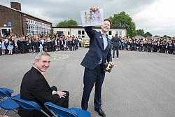 © Licensed to London News Pictures . 03/07/2014 . Leeds , UK . The Deputy Prime Minister , NICK CLEGG MP , at Ireland Wood Primary School in Leeds today (Thursday 3rd July 2014) shows a gift he received from students , with Greg Mulholland , Liberal Democrat MP for Leeds North West (sitting on left) . The Liberal Democrat leader and MP for Sheffield Hallam watches a Grand Depart school event with children taking part in cycling time trials and singing the the Tour de France anthem . Photo credit : Joel Goodman/LNP