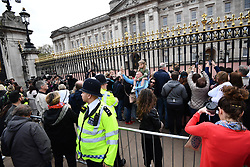 © Licensed to London News Pictures. 23/04/2018. London, UK. Members of the public gather to watch as  A notice is placed outside Buckingham Palace following the announcement of the Birth of a baby boy to The Duchess of Cambridge and Prince William. Photo credit: Ben Cawthra/LNP
