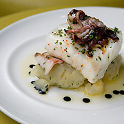 The Merluzzo - Olive Oil Crushed Potatoes, Squid Ink Vinaigrette Grilled Atlantic Cod, Calamari, at Bibiana. Bibiana is the latest restaurant by Ashok Bajaj, the New Delhi native and king of the downtown power meal.
