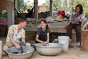 ICS volunteers Dan Hensman & Sokuntheary Nhel hand washing their clothes in the yard of their host home, watched by their host home mother. Banteay Char, near Battambang, Cambodia.