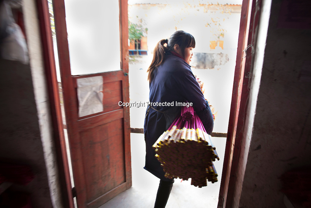 Hunan, Liuyang, Dec. 19..2013 : LUO YUNLIAN, 34, a worker, assembles  fireckrackers for the Western market in a factory .