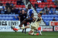 Giuseppe Bellusci of Leeds United tackles Sheyi Ojo of Wigan Athletic. Skybet football league championship match , Wigan Athletic v Leeds Utd at the DW Stadium in Wigan, Lancs on Saturday 7th March 2014.<br /> pic by Chris Stading, Andrew Orchard sports photography.