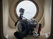 An underwater housing for a dslr camera and GoPro rests near a porthole window.