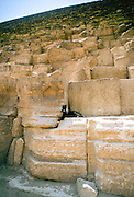A lone goat sheltering among the stones of the Great Pyramids in Egypt