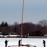 (PSTORE) Red Bank 1/28/2004 The huge mast of the Vanguard A class boat towers above those standing on the ice outside of the clubhouse after it was raised into place.  The mast originally 36 feet has been trimmed through the years and now is in the area of 32 feet of solid wood.  Michael J. Treola Staff Photographer..