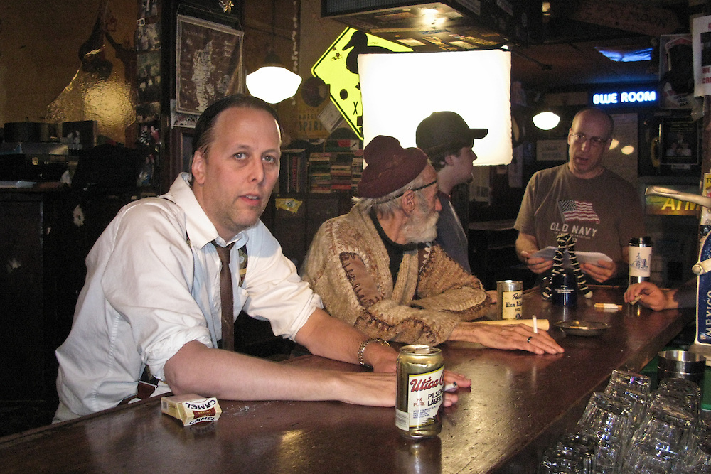 Director Michael Kleven confers with Associate Producer Billy Debaste while actors Michael Brill and David Locke look on while preparing for another scene from The Professional Man. Filmed at The historic Blue Moon Tavern in Seattle Washington