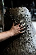 Agnone, Molise - A worker at Marinelli Pontificial Foundry spreads clay on the outside structure of the bell to shape the interior part of the bell.<br /> <br /> Ad Agnone, la tradizione di forgiare e fondere i metalli rislae a 2500 anni fa, al Medioevo. La fonderia Marinelli, con oltre otto secoli di attivit&agrave;, &egrave; l&rsquo;officina in cui vengno prodotte camoane pi&ugrave; antica del mondo. Ad oggi i Marinelli continuano questa secolare tradizione forgiando campane dai bellissimi rilievi artistici e dalla perfetta sonorit&agrave;. Nel 1924, Papa Pio XI, concesse alla famiglia Marinelli di effiggiarsi dello stemma Pontificio.<br /> Ph. Roberto Salomone