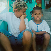 Two small boys sitting on some steps, one hiding his smile the other looking unimpressed, Brazil, 1990's