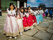 """10 OCTOBER 2018 - SEOUL, SOUTH KOREA:  At Gyeongbokgung Palace wear """"Hanbok"""" style clothing. Hanbok is traditional Korean clothing, originally popular in the late Joseon dynasty, before the Japanese conquest of Korea. It is known for vibrant colors and simple lines without pockets. The term literally means """"Korean clothing"""", but hanbok usually refers specifically to clothing of the Joseon period. The South Korean government encourages people to wear Hanbok clothing to festivals and cultural celebrations and some museums give free admiccion to people wearing Hanbok clothing.       PHOTO BY JACK KURTZ"""