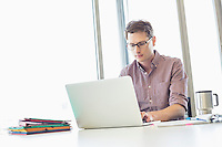 Mid-adult businessman working laptop at desk in creative office