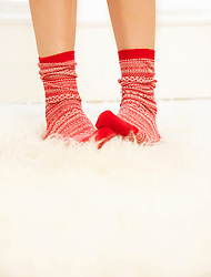 Woman's Feet with Red and White Wool Socks on Fluffy Rug