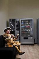 King Henry VIII reading on sofa near vending machine
