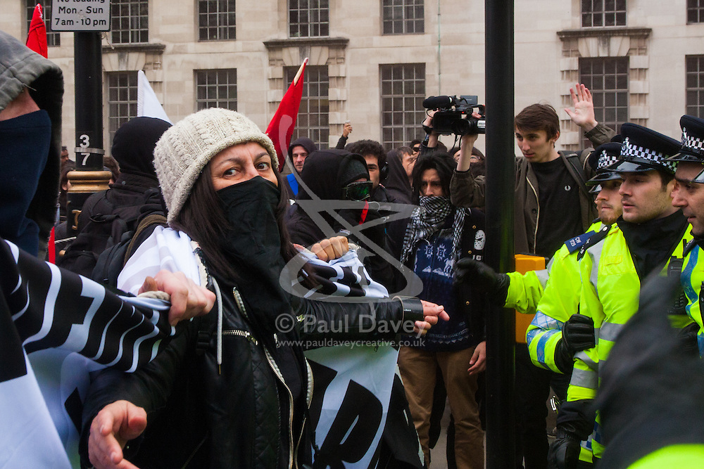 Whitehall, London, April 4th 2015. As PEGIDA UK holds a poorly attended rally on Whitehall, scores of police are called in to contain counter protesters from various London anti-fascist movements. PICTURED: Anti-fascists taunt the police during a stand-off after another failed attempt to reach the PEGIDA rally.