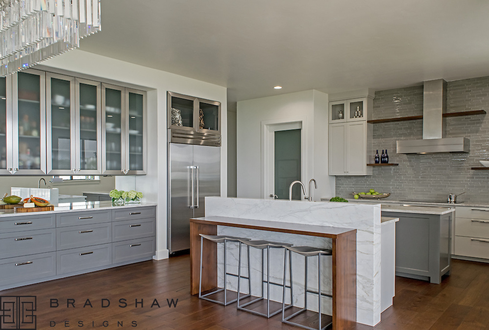 1st Place Award!  ASID Pinnacle of Design 2016, Kitchen New Construction. Award-winning modern hill country kitchen dazzles with mirror splash, calacatta marble slab on island, and stainless cabinet doors for a light bright and fresh feel.   Bradshaw Designs kitchen designer in San Antonio Texas.